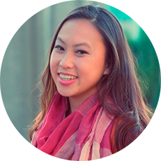 Image: Circular headshot of Emily Nguyen, an Asian American woman with dark hair, brown eyes, smiling and wearing as multi-colored scarf with blurred out green background.