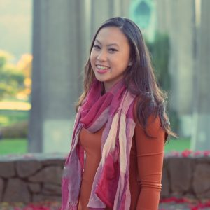 Image: Circular headshot of Emily Nguyen, an Asian American woman with dark hair, brown eyes, smiling and wearing as multi-colored scarf standing in front of a stone wall and trees.