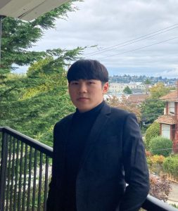 Image: Headshot photo of an Asian American man with dark hair, brown eyes, wearing a black sport coat with a black shirt. The background is overlooking a neighborhood in Seattle.