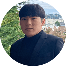 Image: Circular headshot photo of an Asian American man with dark hair, brown eyes, wearing a black sport coat with a black shirt. The background is overlooking a neighborhood in Seattle.