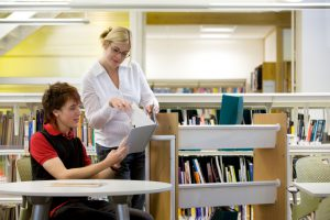 Image: Student in library is aided by a librarian.