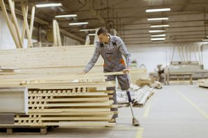 young man with an artificial leg is working at furniture factory