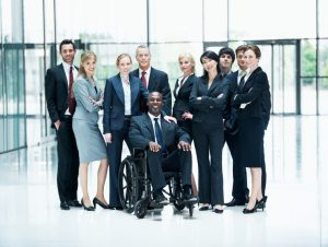 Image: Group of businesspeople standing around their colleague sitting in a wheelchair while smiling