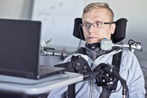 Image: Student who uses a wheelchair and associated equipment looking at a computer, sitting at a desk.